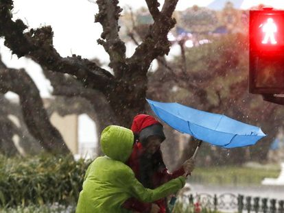 Tourists shield themselves from the rain in San Sebastián.