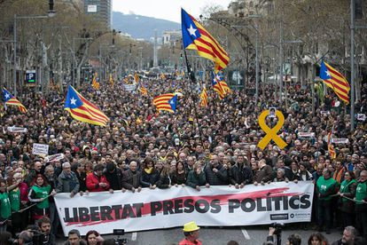 """Protesters in Barcelona carry a sign demanding """"freedom for political prisoners."""""""