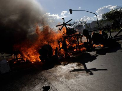 Protesters set fire to barricades in Brasilia using office furniture looted from ministry buildings.