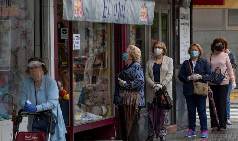 Women wearing masks wait in line to enter a store in Seville on Tuesday.