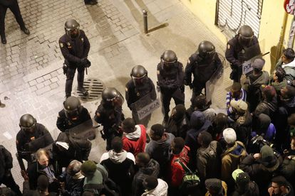 Riot police face protesters in Lavapiés.