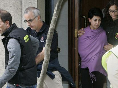 The parents of Asunta are escorted from their property by police.