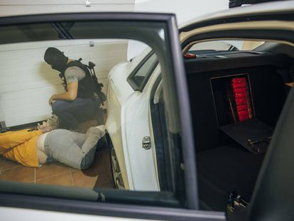 A police officer arrests a member of a drug ring found stashing packages of cocaine into a hiding place in the back seat of a car in Pontevedra.