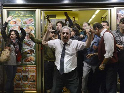 Barman Alberto Casillas faces up to police outside his restaurant at Tuesday's demonstrations.