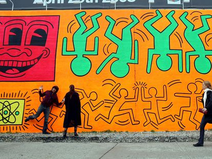 People walk by a recreation of an untitled mural painted by artist Keith Haring in New York.