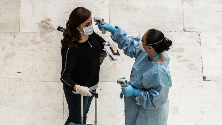 A traveler has her temperature taken at Madrid-Barajas airport.
