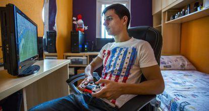 José Luis Flores plays on his PlayStation in his room.