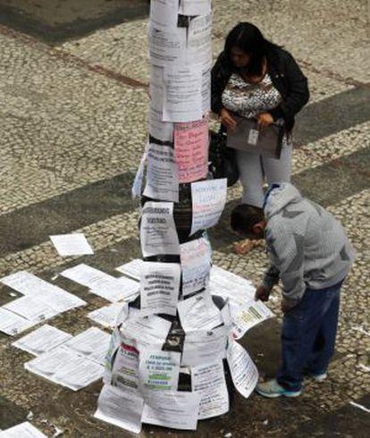 Two people read job postings on a street in São Paulo, Brazil.