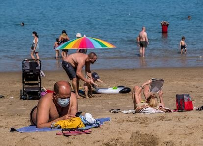 Beachgoers wear face masks in Las Canteras beach in Tenerife.