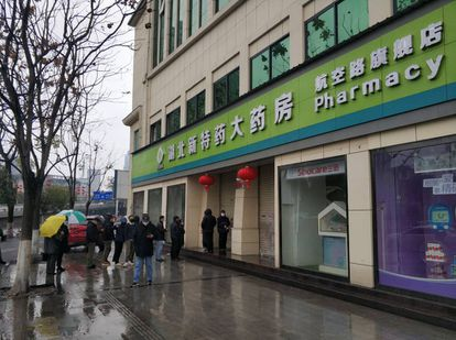 People wait outside a pharmacy in Wuhan.