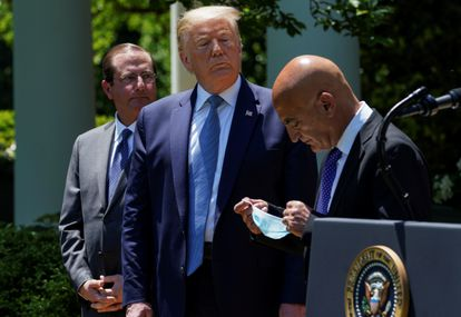 Donald Trump looks on as former GlaxoSmithKline pharmaceutical executive Moncef Slaoui removes his face mask during a coronavirus response event in the Rose Garden at the White House in May of this year.