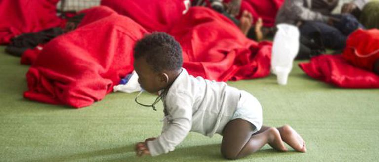 A baby crawls on the floor of a former sports center turned into an immigrant shelter in Tarifa last August.