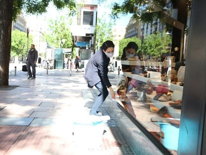 A worker cleaning the display window of a shoe store in Madrid.