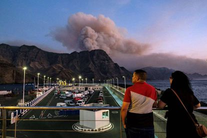Two people in the port ofAgaete watch smoke rise from Pinar de Tamadaba.