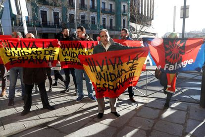 """A group of protesters holds banners with the message """"Long live Spanish unity"""" in front of the Supreme Court. One of them (r) holds a flag from the fascist-inspired Falange party."""