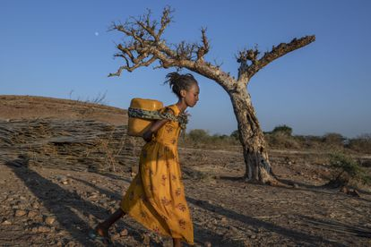 A young woman who fled the conflict in Ethiopia's Tigray region carries water at Umm Rakouba refugee camp in Qadarif, eastern Sudan.