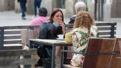A woman smokes at a sidewalk cafe in Galicia, which has banned smoking in all public spaces when social distancing measures cannot be respected.