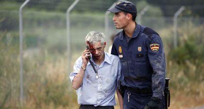 A police officer escorts train driver Francisco José Garzón shortly after the derailment.