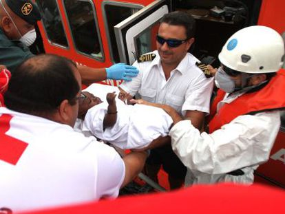 Red Cross volunteers move a baby who reached Tarifa by boat on Monday.