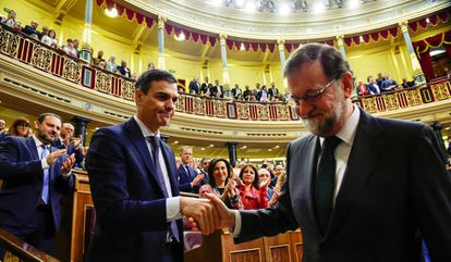 Spain's new Prime Minister Pedro Sanchez shakes hands with Mariano Rajoy.