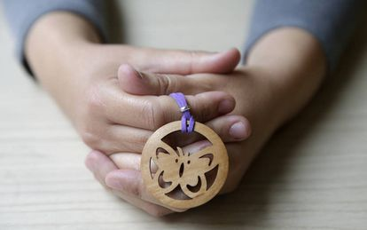 Itziar Prats holds a wooden butterfly, which was sent to her by a stranger in tribute to the victims of gender violence.