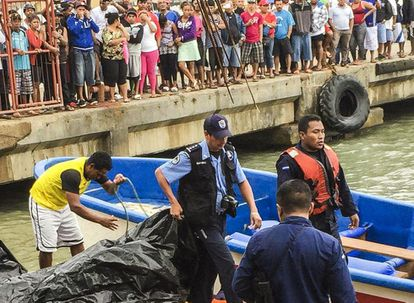 Local police on Corn Island, Nicaragua help recover the bodies of Saturday's boating accident.