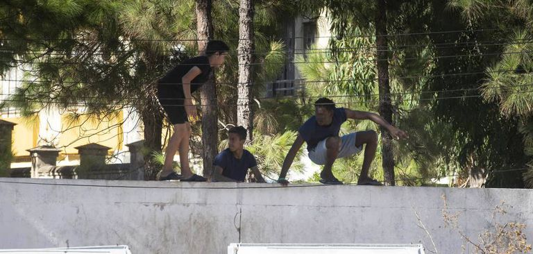 A group of minors jump the fence at a shelter in La Línea (Cádiz).