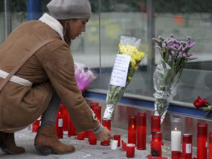 A girl lays flowers at a memorial for the four deceased in the Madrid Arena accident.