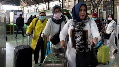 Tourists with face masks arrive at the train station in Valencia.