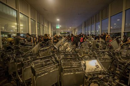 Protesters blocked the entrance with luggage carts.