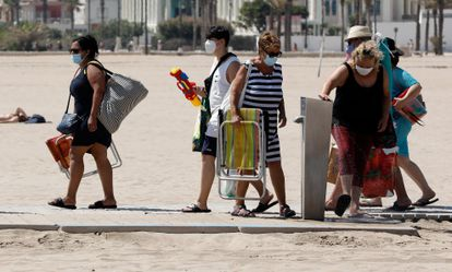 A group of people wear face masks in Malvarrosa beach in Valencia.