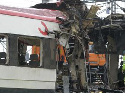 Investigators look at the damage the March 11, 2004 bomb blast caused to commuter train cars in Madrid the day after the tragedy.