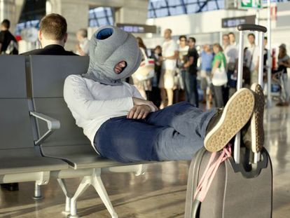 A traveler naps with the aid of the Madrid-designed Ostrich Pillow.