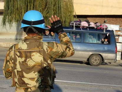 A Unifil soldier waves to a school bus in the south of Lebanon in December.