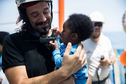 A rescue worker with a baby on the Aquarius.