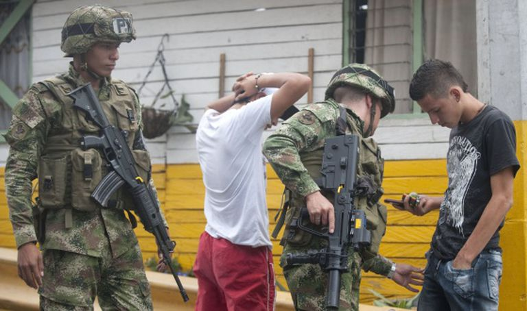 Military police search two young men.