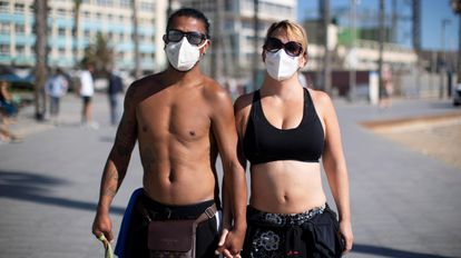 Two people wear face masks in Barcelona in May.