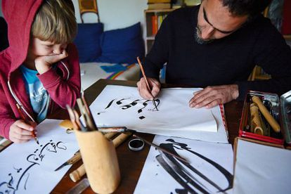 Ali writes calligraphy under the watchful eye of his son.