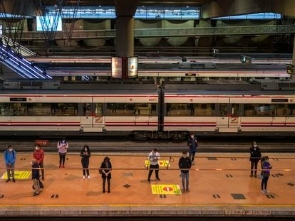 Passengers wait at a platform of Atocha train station in Madrid.