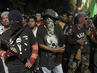 Hooded men stand guard while suspects are turned over to police in Ayutla de los Libres.