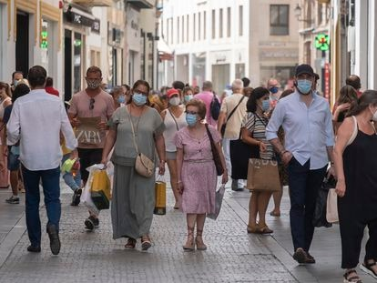 People wear face masks as they walk down the shopping strip in Seville.