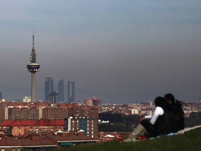 A couple look out at a smog-stained Madrid skyline.