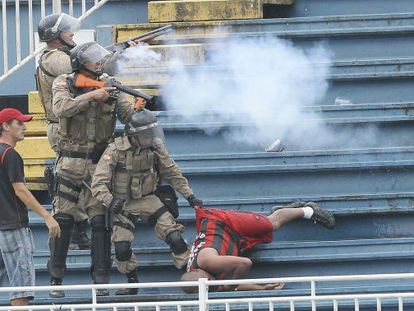 Police fire tear gas at warring supporters as another is dragged away during the Atlético Paranaense-Vasco de Gama match.