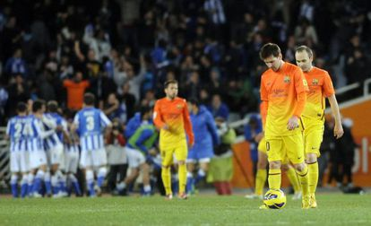 Barcelona's Lionel Messi (2nd R) and Barcelona's midfielder Andrés Iniesta (R) react after Real Sociedad scored its third goal.