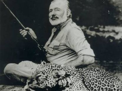 Ernest Hemingway stands beside a dead leopard in 1953.