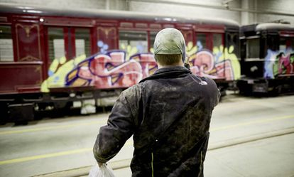 One of the graffiti artists takes a picture of the recently painted 1926 train.