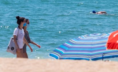 Beachgoers wearing face masks on the beach in La Antilla, in Andalusia's Huelva province.
