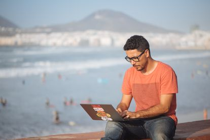Engineer Carlos Rey-Moreno working remotely from Las Canteras beach in Gran Canaria.