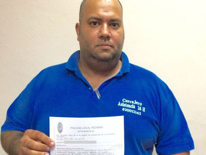 Juan Carlos Puyoles holds up the police complaint.