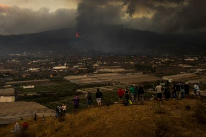 People observe the volcano from La Laguna on Tuesday.